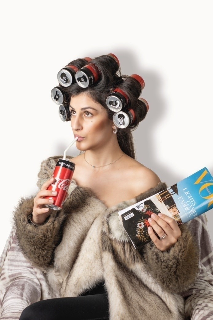 A woman curling her hair using Coca-cola bottles